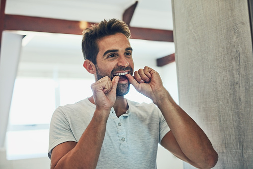 Man flossing to help prevent gum disease